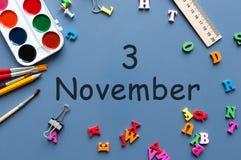 11月3日 天3去年秋天月,在蓝色背景的日历与学校用品 企业主题 免版税库存照片
