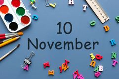 11月10日 天10去年秋天月,在蓝色背景的日历与学校用品 企业主题 库存图片