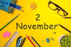 11月2日 天2去年秋天月,在黄色背景的日历与办公用品 企业主题 免版税图库摄影