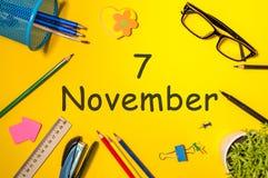 11月7日 天7去年秋天月,在黄色背景的日历与办公用品 企业主题 免版税库存照片
