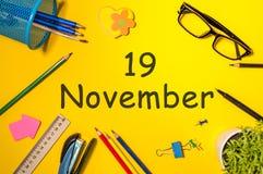 11月19日 天19去年秋天月,在黄色背景的日历与办公用品 企业主题 免版税库存图片