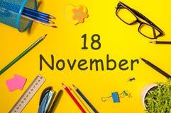 11月18日 天18去年秋天月,在黄色背景的日历与办公用品 企业主题 免版税库存照片