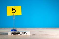2月5日 天5 2月月,在一点标记的日历在蓝色背景 花雪时间冬天 文本的空的空间 库存图片