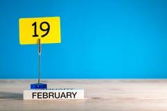 2月19日 天19 2月月,在一点标记的日历在蓝色背景 花雪时间冬天 文本的空的空间 库存图片
