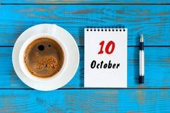 10月10日 天10 10月月,在作业簿的日历与在学生工作场所背景的咖啡杯 秋天时间 库存照片