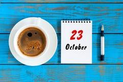 10月23日 天23 10月月,在作业簿的日历与在学生工作场所背景的咖啡杯 秋天时间 库存照片
