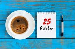 10月25日 天25 10月月,在作业簿的日历与在学生工作场所背景的咖啡杯 秋天时间 库存图片
