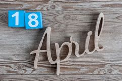 4月18日 天18 4月月,在木背景的颜色日历 春天…上升了叶子,自然本底 免版税库存图片