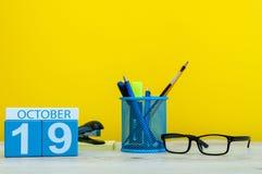 10月19日 天19 10月月,在老师的木颜色日历或学生桌,黄色背景 秋天 免版税库存照片