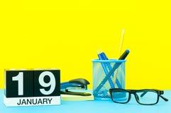 1月19日 天19 1月月,在黄色背景的日历与办公用品 花雪时间冬天 免版税库存图片