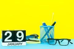 1月29日 天29 1月月,在黄色背景的日历与办公用品 花雪时间冬天 库存照片