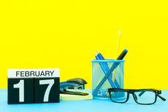 2月17日 天17 2月月,在黄色背景的日历与办公用品 花雪时间冬天 免版税图库摄影