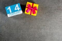 2月14日 天14 2月月,在黑暗的背景的日历与礼物盒 圣徒华伦泰` s天 空的空间 免版税库存照片