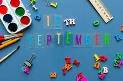 9月12日 天12月,回到学校概念 在老师或学生工作场所背景的日历与学校 免版税库存照片