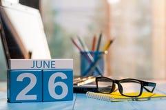 6月26日 天26月,在旅行家工作场所背景的木颜色日历 新的成人 文本的空的空间 库存照片