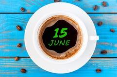 6月15日 天15月,在早晨咖啡杯写的每天日历在蓝色木背景 背景概念框架沙子贝壳夏天 库存图片