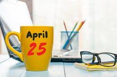 4月25日 天25月,在早晨咖啡杯,营业所背景,有膝上型计算机的工作场所的日历和 免版税库存照片