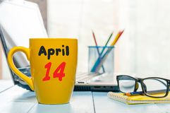 4月14日 天14月,在早晨咖啡杯,营业所背景,有膝上型计算机的工作场所的日历和 免版税库存图片
