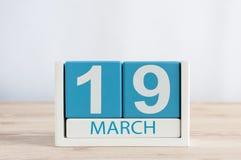 3月19日 天19月,在木桌背景的日历 日森林春天郊区结构 地球小时和国际客户 免版税库存照片
