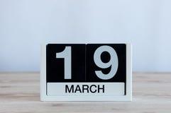3月19日 天19月,在木桌背景的每天日历 日森林春天郊区结构 地球小时和国际性组织 库存图片