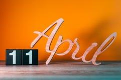 4月11日 天11月,在桌上的每日木日历有橙色背景 春天概念 库存照片