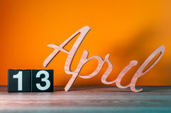 4月13日 天13月,在桌上的每日木日历有橙色背景 春天概念 免版税库存图片