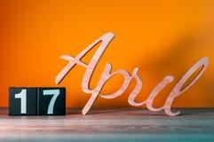 4月17日 天17月,在桌上的每日木日历有橙色背景 春天概念 图库摄影