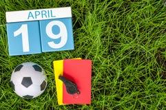 4月19日 天19月,在橄榄球绿草背景的日历与足球成套装备 春天…上升了叶子,自然本底 免版税库存图片
