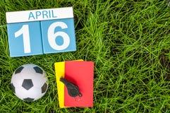 4月16日 天16月,在橄榄球绿草背景的日历与足球成套装备 春天,空的空间 免版税库存图片