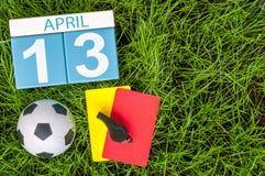 4月13日 天13月,在橄榄球绿草背景的日历与足球成套装备 春天,空的空间 免版税图库摄影
