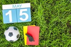 5月15日 天15月,在橄榄球绿草背景的日历与足球辅助部件 春天,空的空间 免版税库存照片