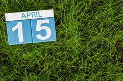 4月15日 天15月,在橄榄球绿草背景的日历 春天,文本的空的空间 免版税库存图片