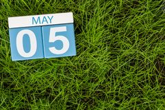 5月5日 天5月,在橄榄球绿草背景的木颜色日历 春天,文本的空的空间 图库摄影