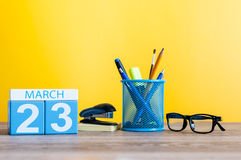 3月23日 天23月,在淡黄色背景,有办公室suplies的工作场所的日历 春天,空 库存照片