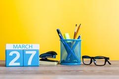 3月27日 天27月,在淡黄色背景,有办公室suplies的工作场所的日历 春天,空 图库摄影