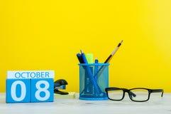 10月8日 天8月,在老师的木颜色日历或学生桌,黄色背景 秋天时间 空 免版税库存图片
