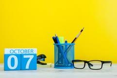 10月7日 天7月,在老师的木颜色日历或学生桌,黄色背景 秋天时间 空 免版税库存照片