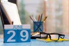 6月29日 天29月,在苦干者工作凳背景的木颜色日历 新的成人 文本的空的空间 库存图片