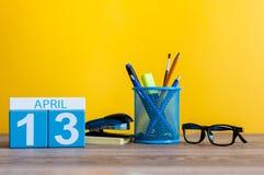 4月13日 天13月,在营业所桌,工作场所上的日历有黄色背景 春天…上升了叶子,自然本底 免版税图库摄影
