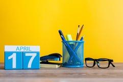 4月17日 天17月,在营业所桌,工作场所上的日历有黄色背景 春天…上升了叶子,自然本底 库存照片