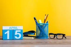 4月15日 天15月,在营业所桌,工作场所上的日历有黄色背景 春天…上升了叶子,自然本底 免版税库存照片