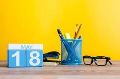 5月18日 天18月,在营业所桌,黄色背景的工作场所上的日历 春天…上升了叶子,自然本底 国际 免版税库存图片