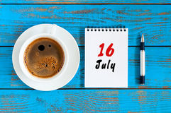 7月16日 天16月,在蓝色木桌背景的日历与早晨咖啡杯 背景概念框架沙子贝壳夏天 免版税图库摄影
