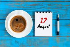 8月17日 天17月,在蓝色背景的日历与早晨咖啡杯 新的成人 独特的顶视图 免版税库存图片