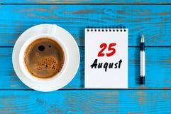 8月25日 天25月,在蓝色背景的日历与早晨咖啡杯 新的成人 独特的顶视图 免版税库存照片