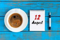 8月12日 天12月,在蓝色背景的活页日历与早晨咖啡杯 新的成人 独特的上面 库存图片