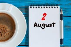 8月2日 天2月,在蓝色背景的活页日历与早晨咖啡杯 新的成人 独特的顶视图 库存照片