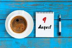 8月9日 天9月,在蓝色背景的活页日历与早晨咖啡杯 新的成人 独特的顶视图 免版税图库摄影
