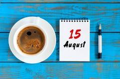 8月15日 天15月,在蓝色背景的活页日历与早晨咖啡杯 新的成人 顶视图 库存图片