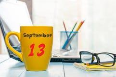 9月13日 天13月,在黄色咖啡杯的日历在律师工作场所背景 秋天时间 空的空间 免版税库存图片